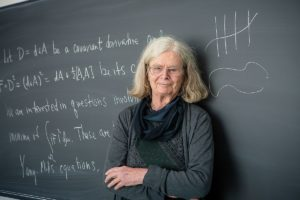 "photo of Karen Uhlenbeck stood in front of a blackboard with Yang-Mills equations"" width="